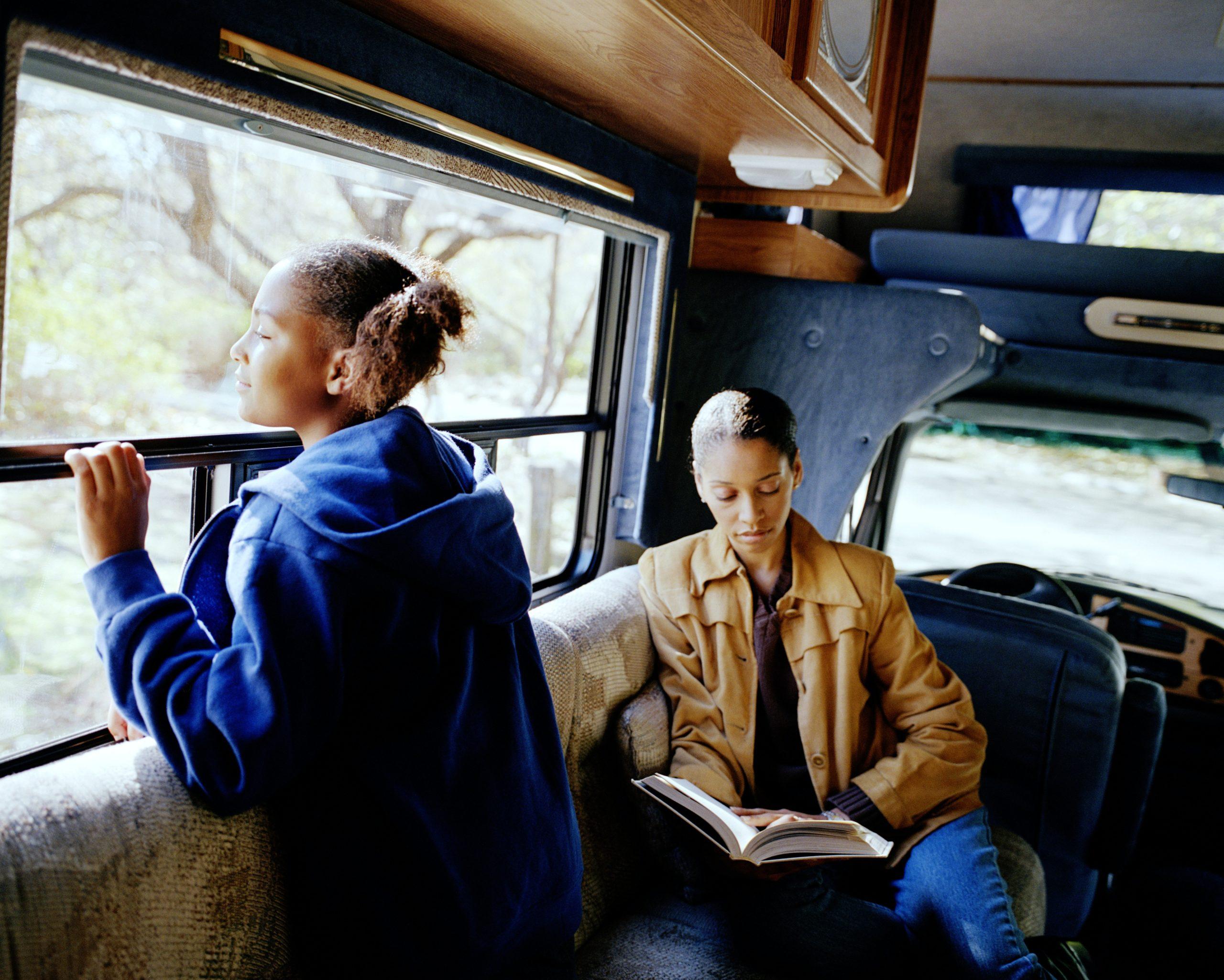Mother and daughter (10-12) relaxing in camper van