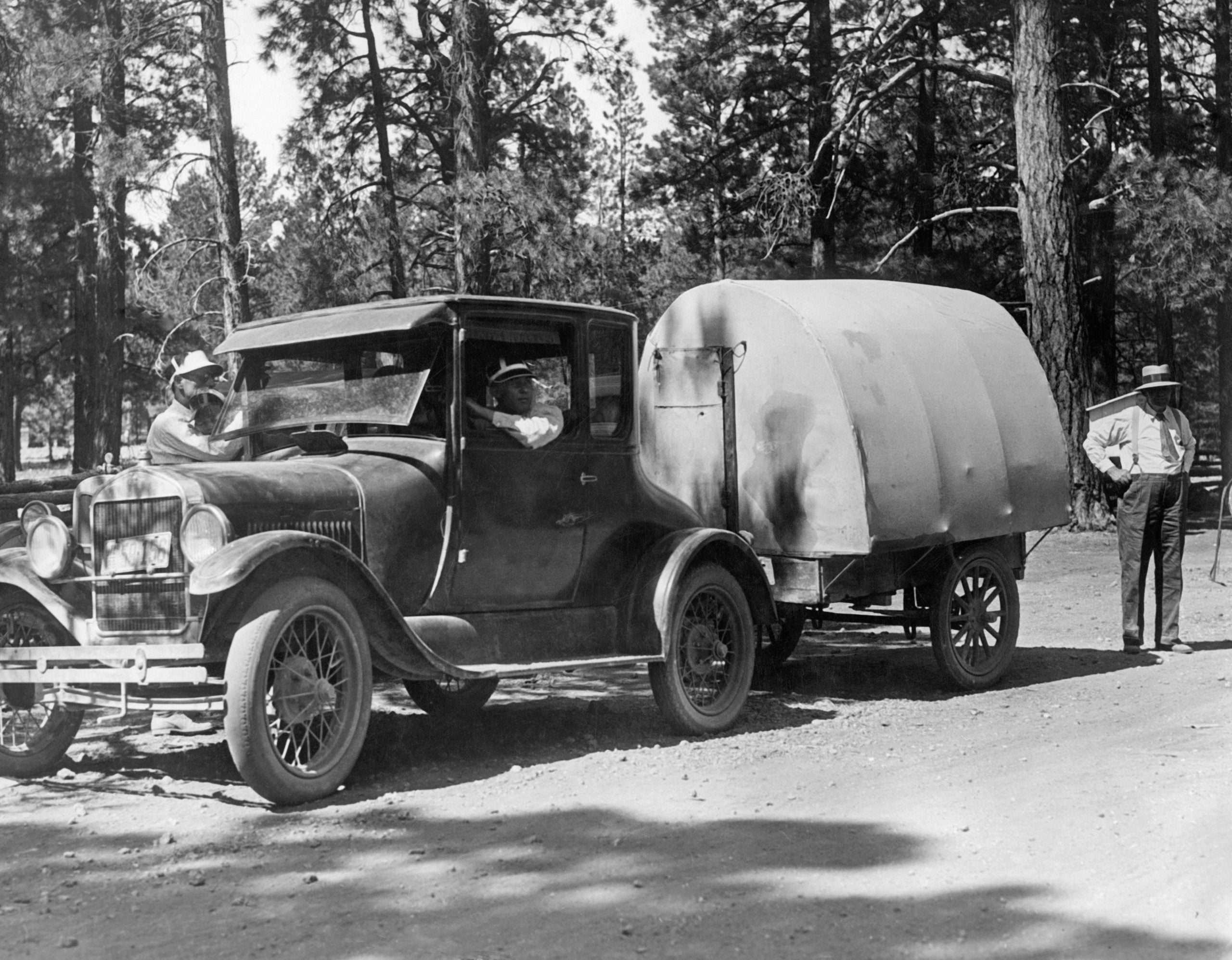 A car pulls an early caravan with tent construction in the Kaibab National Forest on the northern edge of the Grand Canyon.