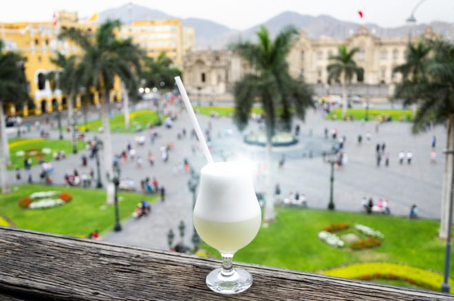 Glass of pisco sour in front of scenic plaza in Peru