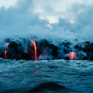 Lava spilling off black cliffs into the ocean in Hawaii