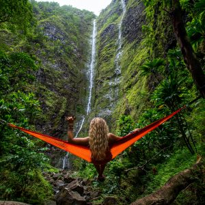 A girl laying on an orange hammock staring at a large waterfall
