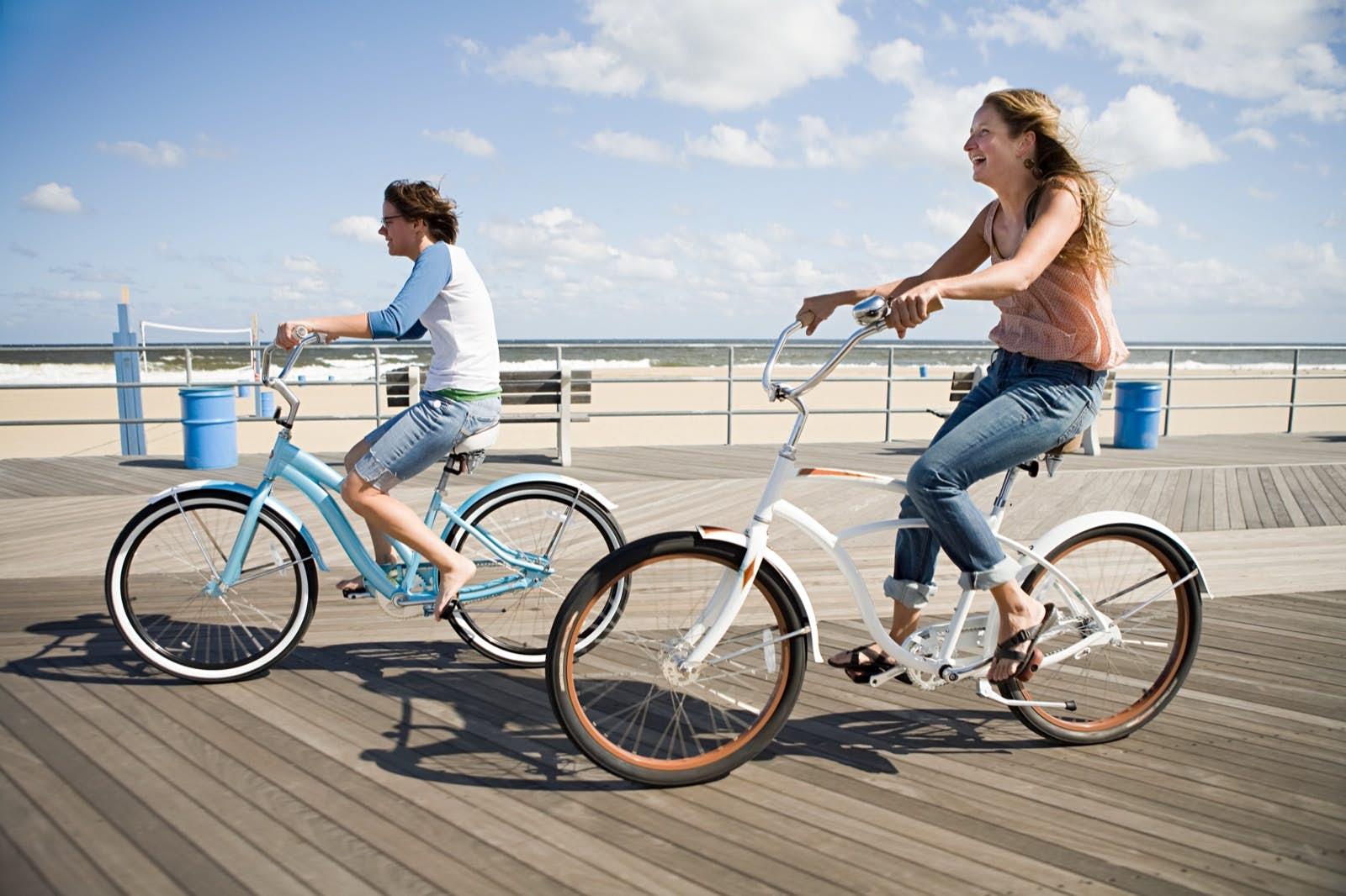 Two people ride bikes down a boardwalk